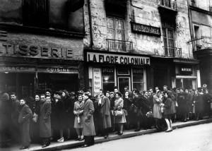 Les Parisiens font la queue devant une boulangerie rue Boissy d'Anglas le 31 décembre 1945, avant le rétablissement de la carte de pain le 1er janvier 1946. On remarque également le magasin LA FLORE COLONIALE spécialisé dans les produits en provenance des colonies et au dessus l'hôtel Boissy d'Anglas. Quelques mois après la fin de la guerre, la relance de la production n'est pas suffisante pour subvenir aux besoins de la population. Le rationnement sur les produits de première nécessité perdure jusqu'en 1949.